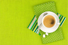 Cup of coffee. White cup of coffee on green linen. Top view Stock Photos