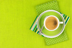 Cup of coffee. White cup of coffee on green linen. Top view Stock Photography