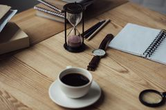 Cup of coffee white hourglass and watch. On workplace Stock Photo
