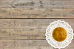 Cup of coffee on white lace napkin on wooden table Stock Photo