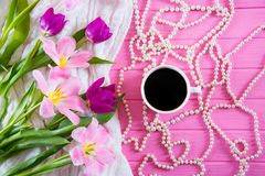 Cup of coffee, white pearl necklace and tender bouquet of beautiful tulips on pink wooden background. Spring morning Stock Photos