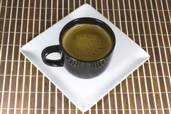 Cup of coffee on a white plate. Hot coffee with foam in the cup on a white plate Stock Photo