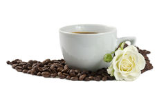 A cup of coffee with white rose and beans isolated. A cup of coffee with white rose and coffee beans isolated on white background Royalty Free Stock Photos