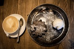 Cup of coffee on a white saucer with chocolate muffin and ice cream. Cup of coffee on white saucer with chocolate muffin and ice cream on wooden background royalty free stock photo