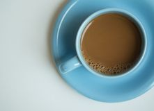 Cup of coffee on white table. Blue cup of coffee on white table Royalty Free Stock Images