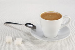 Cup of coffee on a white wicker a mat Royalty Free Stock Images