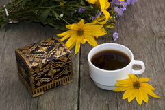 Cup of coffee, wild flowers, casket and yellow flower, still lif Stock Photos