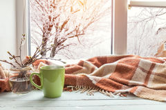 Cup of coffee on the window sill. Cup of coffee, books, branch of cherry tree, wool blanket on windowsill. In the background snow tree pattern on window. Cozy Stock Images