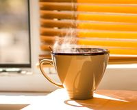 Cup of Coffee on a window sill. Morning cup of coffee on a window sill. Steam above the ceramics cup royalty free stock photos
