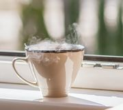Cup of Coffee on a window sill. Morning cup of coffee on a window sill. Steam above the ceramics cup stock photos