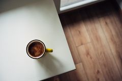 Cup of coffee on the window sill on a sunny day. view from above royalty free stock photography