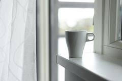 A cup of coffee on the windowsill. Big window. Scandinavian style Royalty Free Stock Images