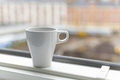 A cup of coffee on the windowsill. Big window. Scandinavian style Stock Photo