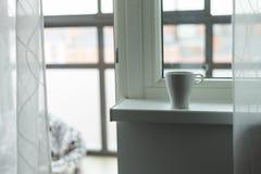 A cup of coffee on the windowsill. Big window. Scandinavian style Stock Image
