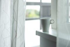 A cup of coffee on the windowsill. Big window. Scandinavian style Stock Photography