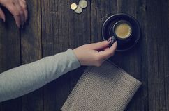 A cup of coffee in a woman`s hand. Lying on a wooden table Stock Image