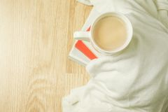 Cup of Coffee on Wood Background with White Cloth and Pile of Books. Cup of coffee, white cloth and stack of books on top of wood background. Morning breakfast Stock Photos