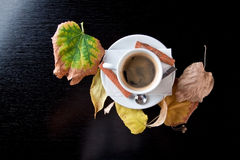 Cup of coffee on wood table with autumn leaves Stock Photos