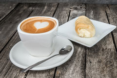 Cup of coffee on wood table with bakery in background Stock Image