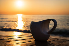 Cup of coffee on wood table at sunset or sunrise beach royalty free stock photos