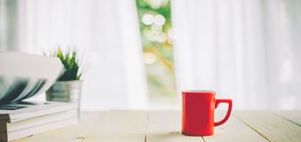 Cup of coffee on wood table top and blur of curtain with window background