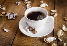 Cup of coffee on wooden background, decorated dried aromatic parts of plants Royalty Free Stock Photos