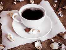 Cup of coffee on wooden background, decorated dried aromatic parts of plants Stock Photography