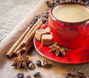 Cup of coffee on wooden background decorated with spices Stock Image