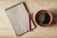 Cup coffee on wooden background with empty note, top view Royalty Free Stock Image