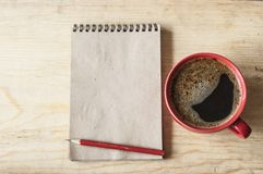 Cup coffee on wooden background with empty note, top view Royalty Free Stock Photos