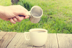 Cup of coffee on a wooden background with hand Stock Image
