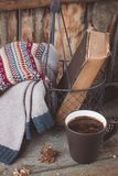 A cup of coffee on the wooden background. Iron basket with a sweater and an old book. Toned. A cup of coffee on the wooden background. Iron basket with a Stock Image