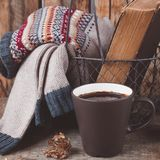A cup of coffee on the wooden background. Iron basket with a sweater and an old book. Toned. A cup of coffee on the wooden background. Iron basket with a Royalty Free Stock Image