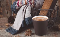 A cup of coffee on the wooden background. Iron basket with a sweater and an old book. Toned. Royalty Free Stock Photo