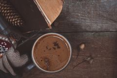 A cup of coffee on the wooden background. Iron basket with a sweater and an old book. Toned. A cup of coffee on the wooden background. Iron basket with a Royalty Free Stock Photos