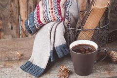 A cup of coffee on the wooden background. Iron basket with a sweater and an old book. Toned. A cup of coffee on the wooden background. Iron basket with a Royalty Free Stock Images