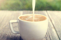 Cup of coffee on a wooden background with milk Stock Photo
