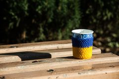 Cup coffee wooden bench covered snow mornimg yellow blue heat knitting. Cup coffee wooden bench covered snow mornimg. A glass with coffee is dressed in a warm Stock Photography