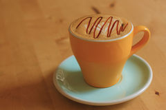 A cup of coffee on the wooden board. Close up of a cup of coffee on the wooden board Royalty Free Stock Photos