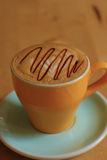 A cup of coffee on the wooden board. Close up of a cup of coffee on the wooden board Stock Photography