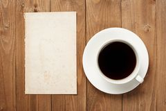Cup of coffee on wooden boards, blank paper sheet with place for text - holiday and greeting concept Royalty Free Stock Images