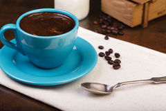 Cup of coffee and wooden containers filled with cofee beans Royalty Free Stock Images