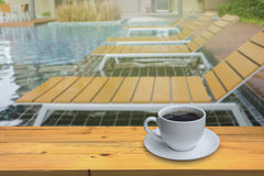 Cup of coffee on the wooden floor and Blurred swimming pool back. Ground stock photo