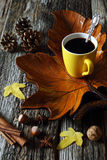 Cup of coffee on wooden maple leaf, nuts and autumn leaves Stock Photography