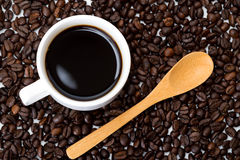 Cup of coffee and wooden spoon. On coffee beans Royalty Free Stock Images