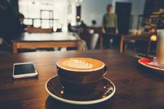 A cup of coffee on wooden surface stock image