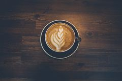 A cup of coffee on wooden surface. Morning time with cappuchino Royalty Free Stock Photos