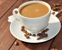 A cup of coffee on a wooden surface decorated with cofee beans  Royalty Free Stock Images