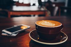 A cup of coffee on wooden surface. With mobiles in cafe Royalty Free Stock Photo