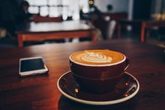 A cup of coffee on wooden surface.  Royalty Free Stock Photography